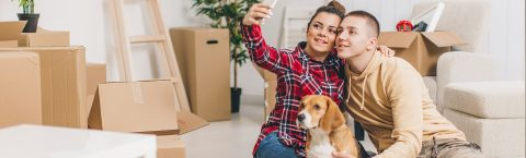 a couple and their dog take a selfie in their new home