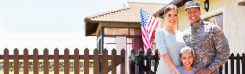 A military family stands proudly in front of their new home.