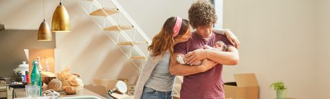 A young couple cradles their baby in their new home
