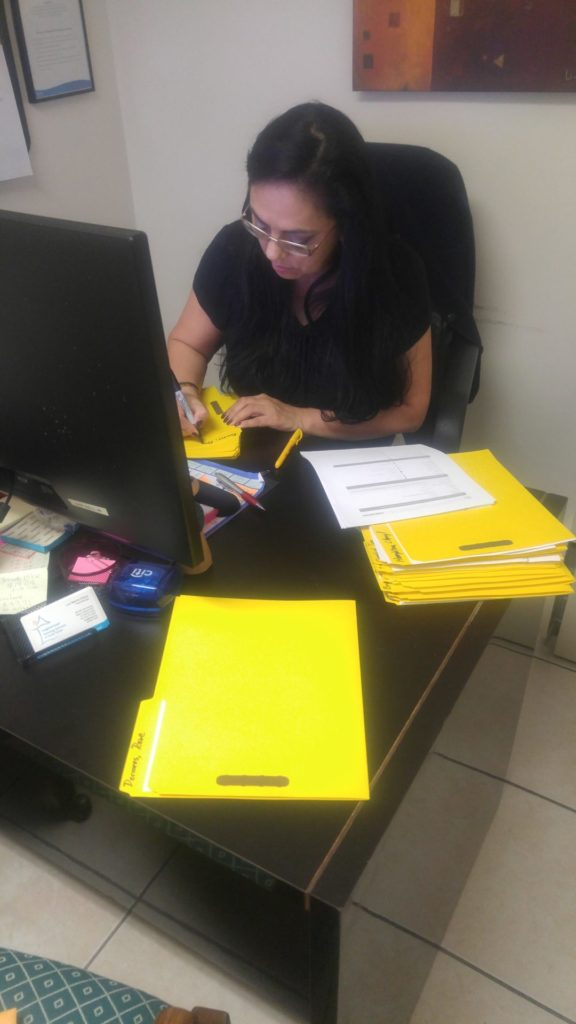 Luz Granja works at her desk as she processes an application for emeregency assistance for a fresident of Broward county.