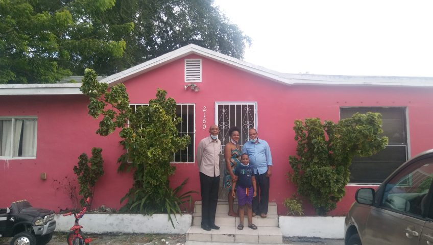 The Jean family stands in front of their new home that was purchased with the help of Neighborhood Housing Services of South Florida